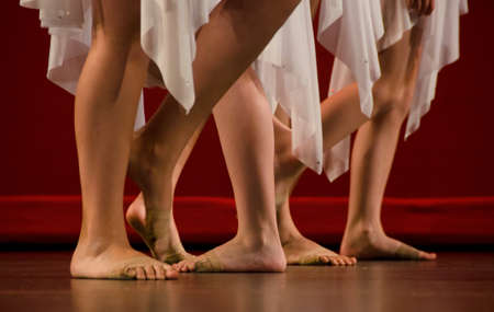 girls feet: Feet of ballet dancers in front of a red wall Stock Photo