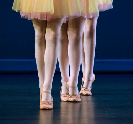 Feet of trio  of dancers in flat shoes and yellow and pink skirts photo