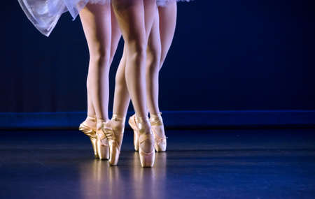 ballet slipper: Feet of trio  of ballerinas on pointe  dark blue floor