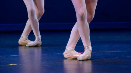 Crossed feet of duo of ballerinas on dark blue floor photo