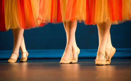 rehearsal: Legs of a trio of ballet dancers in red and yellow skirts