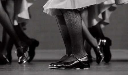 pies bailando: Las piernas de un bailar�n de claqu� en zapatos negros cl�sicos y medias de rejilla