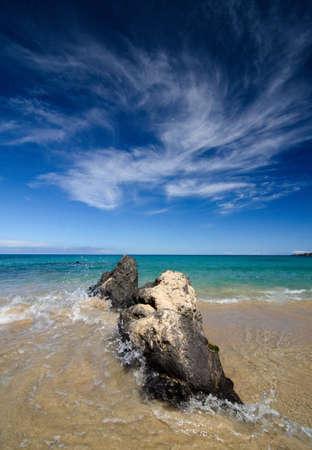 bazalt: Surf breaks at large black basalt rocks at  Puako beach Stock Photo