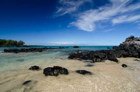 bazalt: Calm waters behind black basalt rocks at  Puako beach Stock Photo