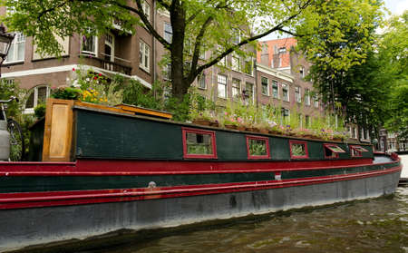 overtaken: Boat house overtaken by a garden at Amsterdam canal Stock Photo