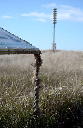 informational: Weathered rope hanging from an informational board with a tsunami warning tower and dunes in the background, Ocean Shores, WA Stock Photo