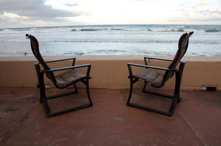 storm tide: Couple of beach chairs at gallery of a beach resort in Southern California