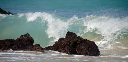 breakaway: Tall morning wave breaks on rocks of beach 69, Big Island, Hawaii Stock Photo