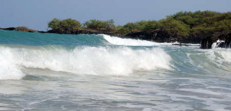 ironwood: Long morning wave breaks on rocks of beach 69, Big Island, Hawaii Stock Photo