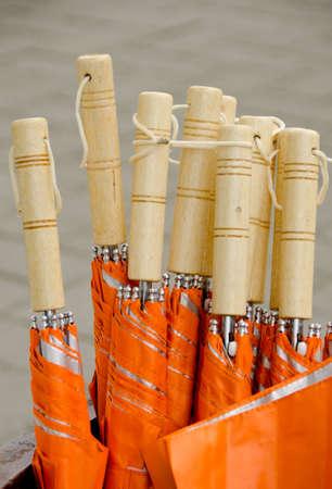 a courtesy: Courtesy orange umbrellas with wooden handles in a bucket in Redmond town center