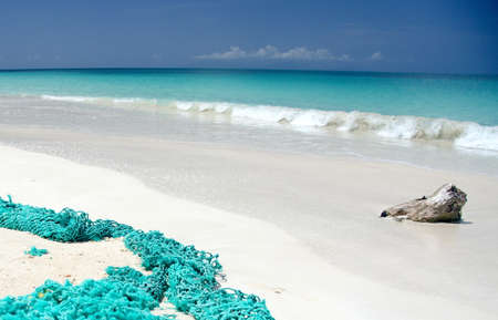 drywood: Abandoned fishnet perfectly matches water colors at Ffryes beach, Antigua