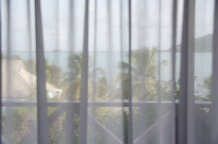 window shades: Jolly harbor and palms behind white shades on window of a cottage at resort in Antigua