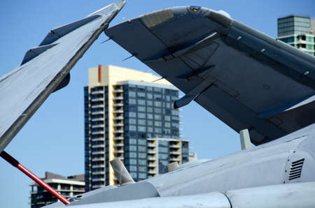 Details of military aircraft in aircraft carrier museum, with downtown buildings in background, San Diego Stock Photo