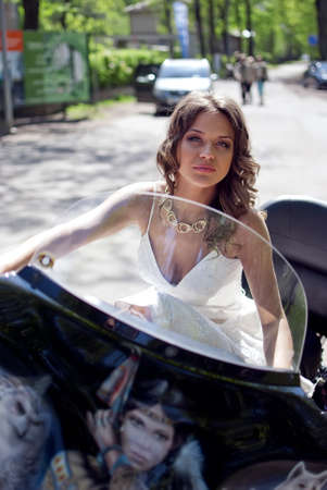 beautiful young bride sitting on a motorcycle photo
