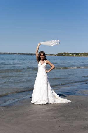 hermosa joven novia tirando el velo cerca del mar Foto de archivo - 9758752