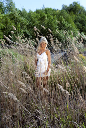 girl in white dress are standing in dry grass at summer daylight photo