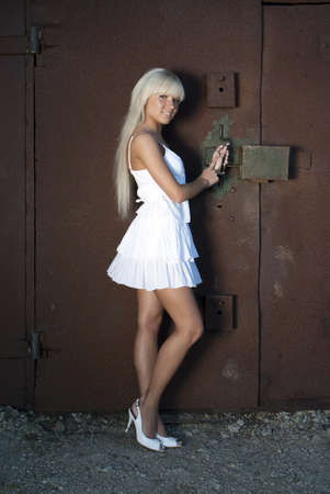 girl in white dress opens old garage with rusty lock photo