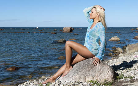 girl in a blue tunic is enjoying summer on the beach, sitting on a rock on the shore photo