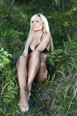 blonde girl in a black bathing suit sitting on the grass in the forest Stock Photo - 9874877