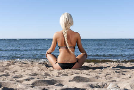 sun bathing: blonde girl in a black bathing suit sits with his back to the beach in the sand and meditate