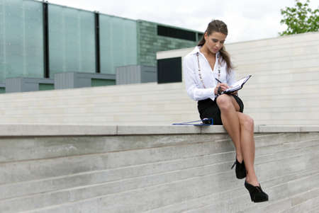 Business woman sitting in a black skirt and sign the document Stock Photo - 9875725