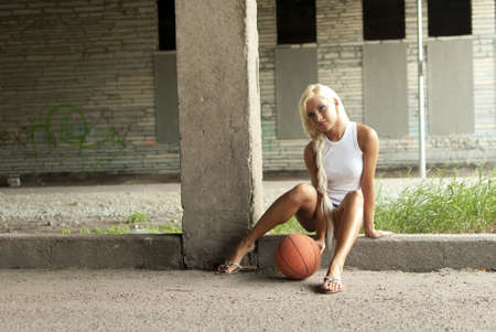 denim shorts: Beautiful blonde girl is sitting with basketball on the street Stock Photo