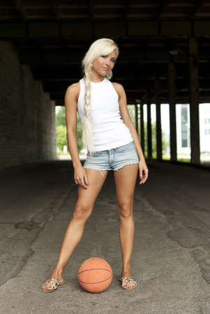 Beautiful blonde girl standing with basketball in the street photo