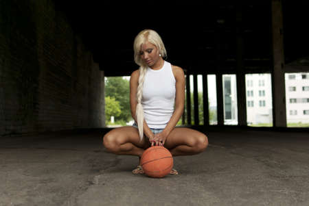 Beautiful blonde girl is sitting with basketball on the street photo