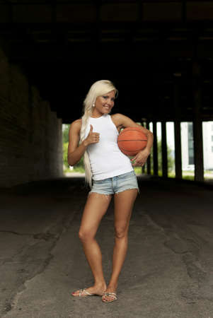 beautiful smiling girl standing with a basketball in the street, thumbs up photo