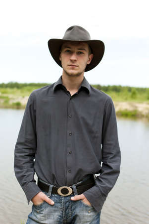man in a cowboy hat standing on the shore of Lake