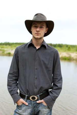cappello cowboy: uomo con un cappello da cowboy in piedi sulla riva del lago