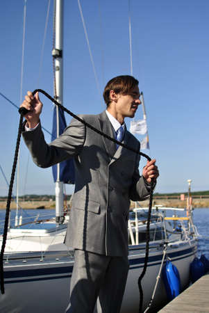 man in a black business suit with a rope in his hands near the yacht photo