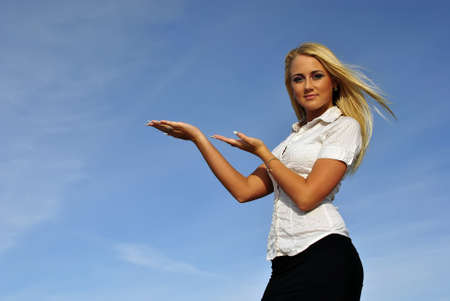 ideally: Blonde girl in a white shirt against the sky. Ideally suited for advertising. Space for text Stock Photo