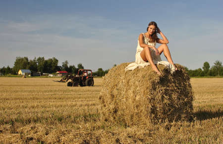 haystacks: girl in a rural clothing sitting on the haystack, tractor on the background. space for text Stock Photo