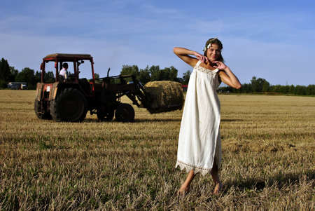 girl in a rural clothing standing on the field, tractor on the background photo