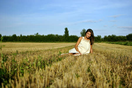 nice girl in national dress, sitting on a field in rural areas, space for text photo