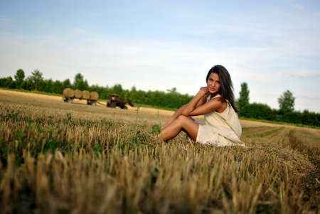 nice girl in national dress, sitting on a field in rural areas, tractor on background, space for text photo