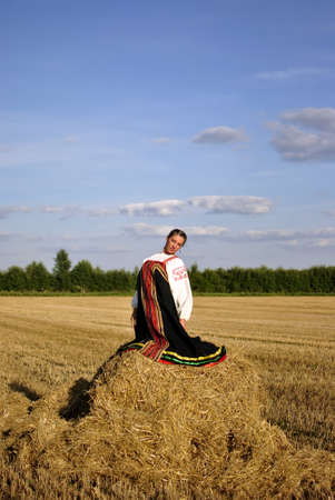 girl in traditional Russian costume sitting on a haystack, space for text photo