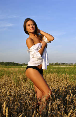 sexy girl in white shirt posing in the field Stock Photo