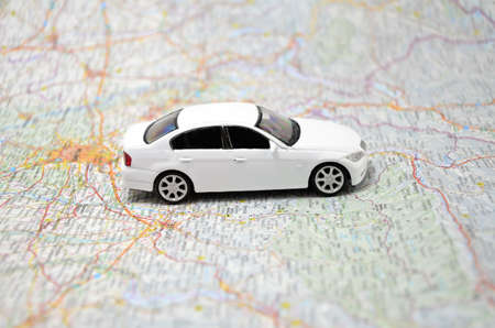 car navigation: concept small white toy car on italy map