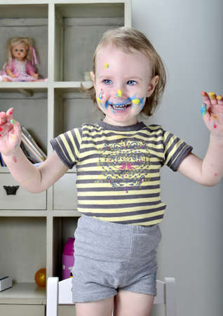funny little girl and colored paints photo