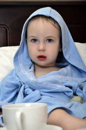 little girl in a blue robe resting on the bed after a shower with a cup of tea photo