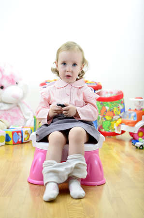 little girl sitting on the potty with a remote control (or mobile phone) in hand photo