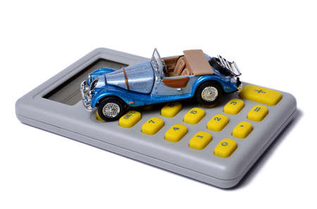 miniature minivan on a calculator isolated on white, concept photo
