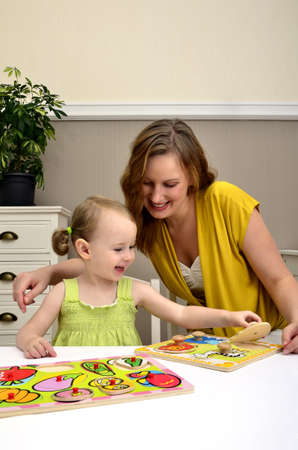 little girl and mom playing in a children puzzle Stock Photo - 11235193