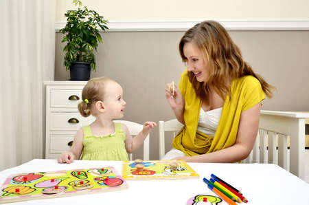 preschoolers: little girl and mom playing in a children puzzle Stock Photo
