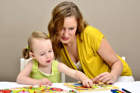 little girl and mom playing in a children puzzle photo