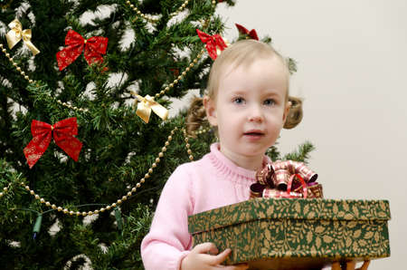 little girl near the christmas tree holding a present photo