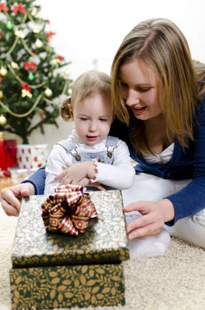 little girl and her mother unpacks the gift at Christmas Stock Photo - 11413197