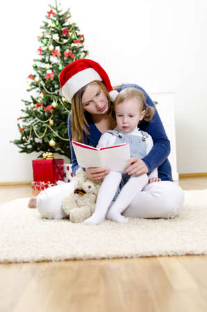 Girl and her mom reading book at Christmas Stock Photo - 11413184